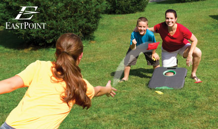 Shop Eastpoint Outdoor Lawn Games - a family playing bean bag toss in a park